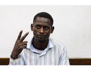 Suleiman Abdul-Adham insolently gestures the V-sign during his arraignment in court