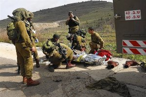 Israeli soldiers evacuate their comrade who was wounded during an explosion near the Druze village of Majdal Shams in the Golan Heights